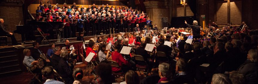 ful orchestra and choir wearing red ties